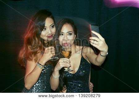 Gorgeous Vietnamese woman taking selfie with her friend