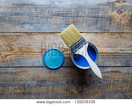 jar with blue paint and brush on the wooden background top view close up