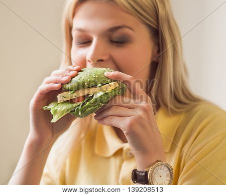 Closeup image of blond woman eating vegan burger in vegan restaurant or cafe. Pretty lady on vegan diet. Healthy food concept.