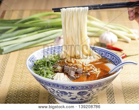 Hot instant noodles with cube beef and herbs on the table