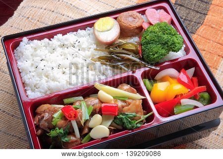 Bento food of plain rice and fried stewed chicken meat eggs broccoli flower and seaweed