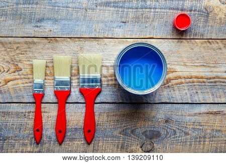 process of preparation for painting wooden floor at home with blue paint top view