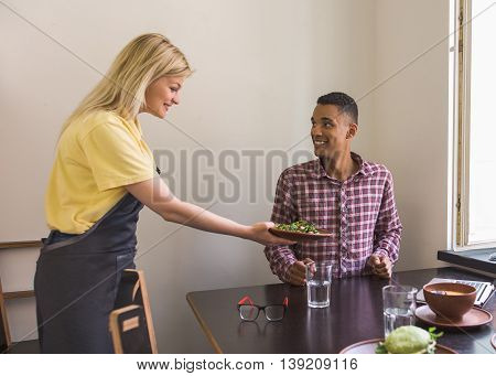 Blond waitress lady giving her guest vegan salad. Vegan concept. Handsome man is being served in vegan restaurant or cafe.