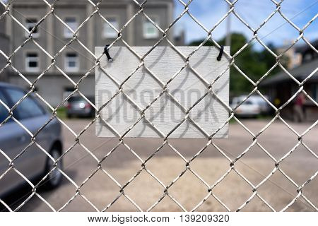 White label hanging on a transparent wire fence of the car park on a background of sky and vehicles