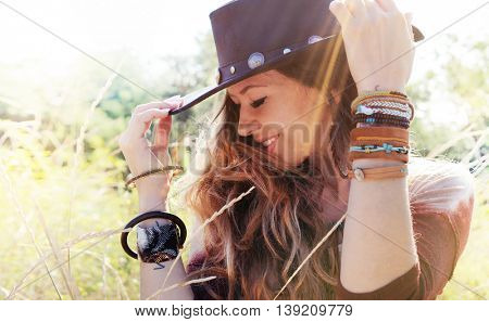 Fashion smiling woman portrait with hat on a head, sunny backlit outdoor photo, boho chic style, hipster style