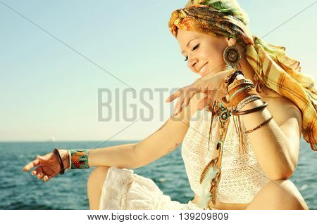 African style fashion woman outdoor portrait, dressed in headband, white lace tank top, necklace and earrings, many leather wristbands, focus on a hand