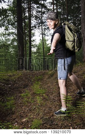 Beautiful girl traveling in the forest with backpack. Adventure travel tourism hike concept.