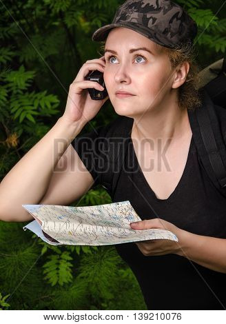 Beautiful girl traveling in the forest with backpack radio and map. Adventure travel tourism hike concept.