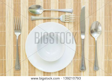Closeup white ceramic dish and cup with stainless fork and spoon on wood mat textured background on dining table in top view group of tableware before dinner