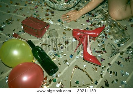 Heels, balloons, sparkles and bottle on the floor after party