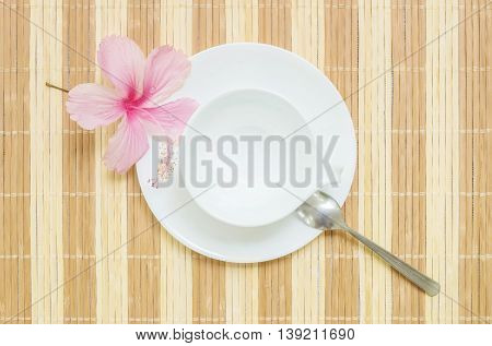 Closeup white ceramic cup for beverage with stainless spoon on blurred wood mat textured background