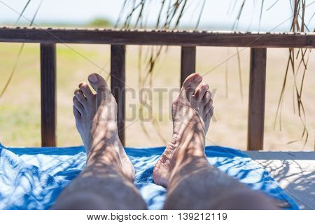 Male feet on lounge with blue hotel towel first person view from bungalow