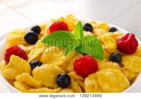 Breakfast with cereal flakes, berries, mint and milk, on white background