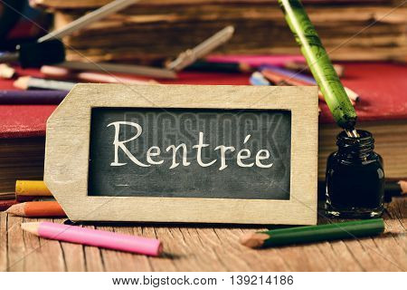 label-shaped chalkboard with the text rentree, back to school in french, some old books and old stationery such as a pen nib or some pencils crayons of different colors, on a rustic wooden table