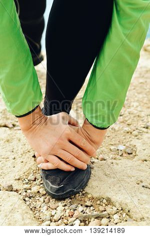 closeup of a young caucasian sportsman wearing sport clothes stretching his legs before or after running outdoors