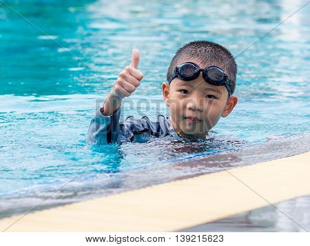 little asian boy holds his thumb up in the pool with goggles
