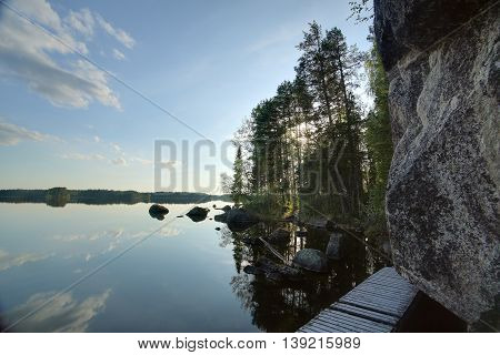 Wooden Bridge Leading Around Rock Cliff At Faangsjoen In Sweden