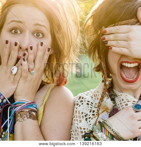 Close up fashion portrait of Two friends have fun , make grimaces ,fun emotions and shows hand signs. Pretty girls wearing summer clothes