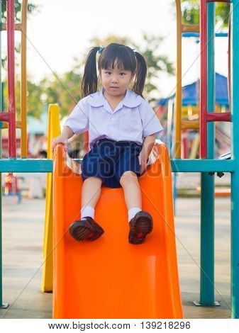 Happy kid asian baby child in school uniform playing on playground slider