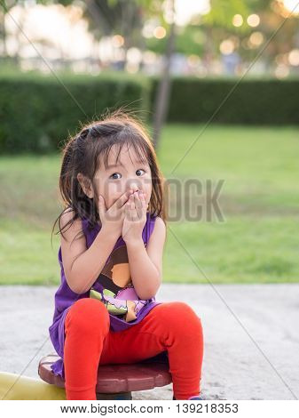 Little asian girl covering her mouth with her hands. Surprised or scared.