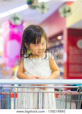 Little cute asian girl in shopping cart