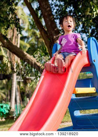 Happy kid asian baby child playing on playground slider
