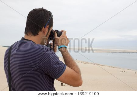 Man taking photos of the sea and the coast of France