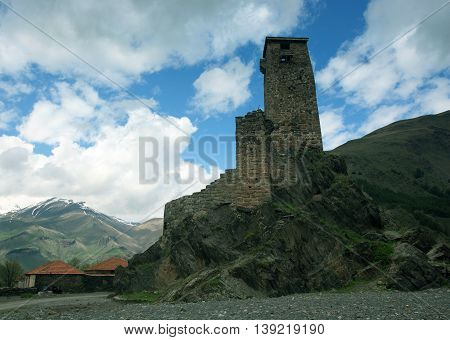 landscape, with Svan guard tower on a background of snow-capped mountain peaks and clouds, Svaneti, Georgia