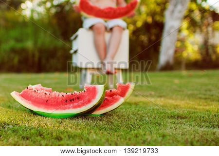 child eating a watermelon outdoor.  a boy holding a piece of  watermelon