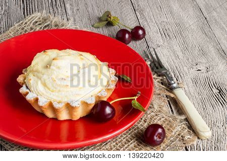Curd dessert with cherries on a red plate on a gray wooden table.