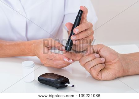 Doctor Measuring Sugar Reading Of Patient With Glucometer