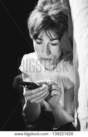 Woman Looking At Phone Before Sleeping