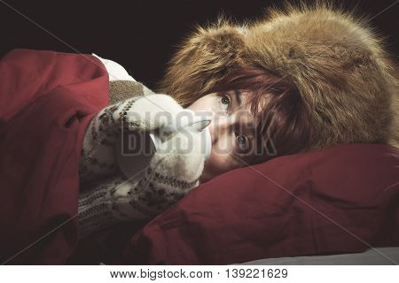 Woman lying in a bed wearing fur hat and mittens drinking from a mug.