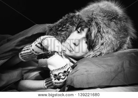 Woman lying in a bed wearing fur hat and mittens carrying a purse.