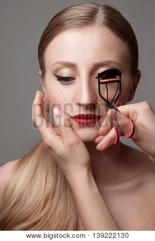 Beautiful woman making curl eyelashes. Beauty Portrait with perfect clean skin and Perfect makeup