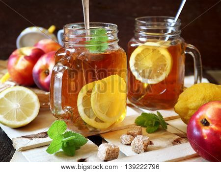 Iced tea with lemon slices and nectarines on rustic background