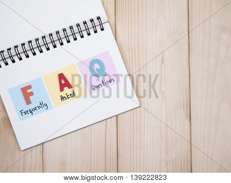 Word spell FAQ and handwriting frequently asked questions on notebook with wood background on top view