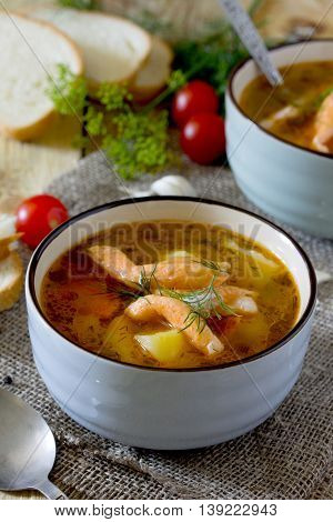 Tomato Soup With Red Fish In A Ceramic Bowl On A Napkin, Tomatoes, Parsley, Bread On A Wooden Boards