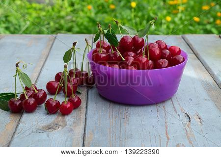 Ripe Cherries In The Crimson Bowl On Wood Background.