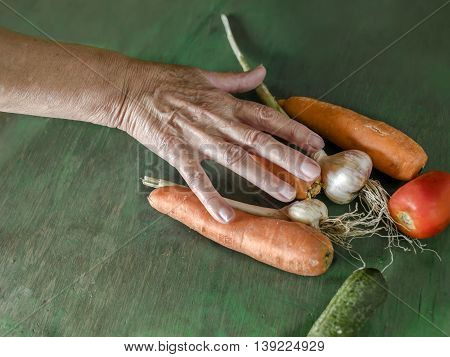 A bunch of fresh vegetables laid on the wooden green table and female hand on top of it selective focus studio shot