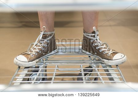 two feet with red shoes on supermarket trolley
