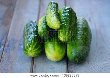 Photos of a pile of fresh picked cucumbers on wooden background.