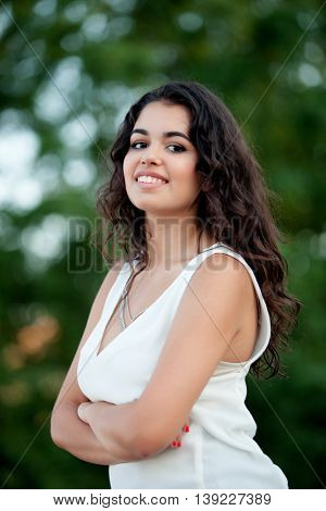 Beautiful brunette girl relaxing in the park wth many plants of background
