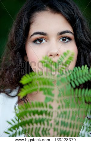 Beautiful brunette girl relaxing in the park with many plants of background