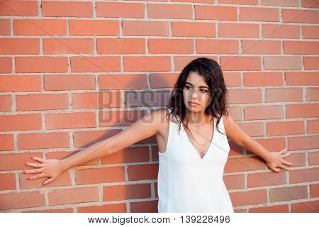 Happy beautiful brunette girl with red wall brick of background