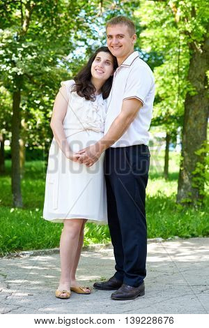 pregnant woman with husband posing in the city park, family portrait, summer season, green grass and trees