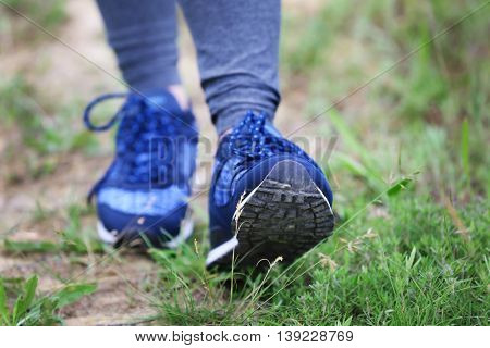 Female hiker walking on a trail at sunny day