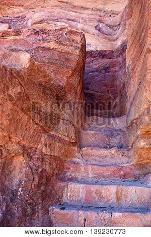 Staircase with stone steps carved into the colorful rock of sandstone. Archaeological site in ancient lost city of Petra Jordan
