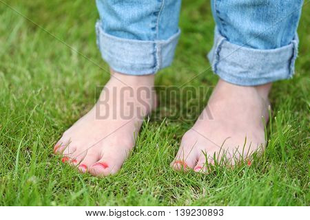 Woman standing  barefoot  on green grass background