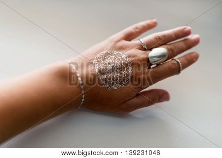 Woman hand with silver jewelry and flash tattooes in indian style. Summer beach fashion. Selective focus